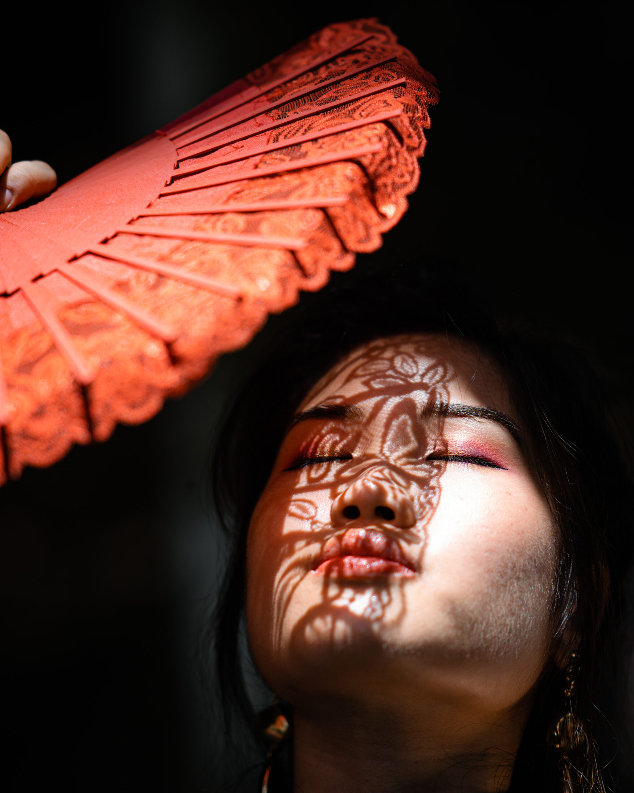 photo-of-woman-cover-her-face-with-hand-fan-2748126